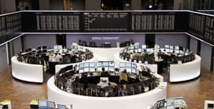 Traders are pictured at their desks in front of the DAX board at the Frankfurt stock exchange September 16, 2013.