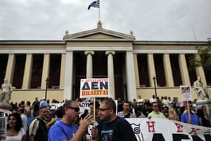 """Greek school teachers hold a sign reading in Greek """"Education is not for sale"""" during a demonstration outside the Athens University on September 16, 2013."""