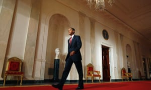 U.S. President Barack Obama walks down the White House cross hall to news conference in the East Room of the White House in Washington, July 22, 2009.