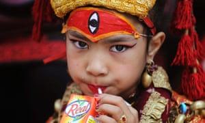 A Nepalese girl wearing traditional dress drinks juice during the Kumari Puja, a mass worship, at the Hanuman Dhoka in Durbar Square in Kathmandu.