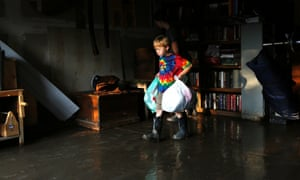 A boy carries clothes from his flooded garage in Longmont, Colorado.