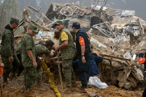 Mexican soldiers and police look for victims of a landslide caused by heavy rains in Xaltepec, Mexico after a tropical storm.