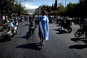 A municipal police demonstrator walks between parked motorcycles blocking a main Athens' avenue outside the Administrative Reform Ministry during a protest on September 17, 2013. As part of the controversial redeployment plan in the country reeling from six years of recession, civil servants have to accept new posts or spend eight months on reduced salaries as alternative posts are found, with the risk of losing their jobs altogether.
