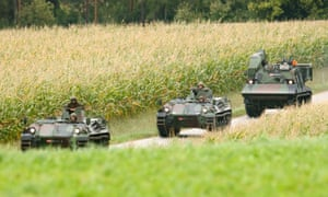 Austrian army armoured personnel carriers approach a crime scene near Melk in Austria. A suspected game poacher shot two policemen and a paramedic after they tried to arrest him in woodland.
