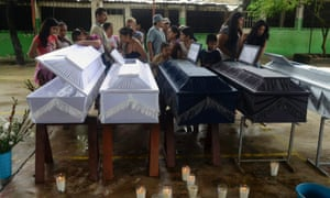 Friends and relatives stand next to coffins containing the remains of members of the Gallegos family after a landslide buried a home on the outskirts of Acapulco, Mexico. Twin storms, Manuel and Ingrid, have left scenes of havoc on both of Mexico's coasts.
