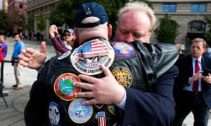 Two men embrace after watching the wreath laying.