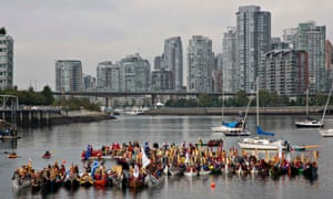 First Nation dugout canoes arrive into False Creek during a gathering of All Nations canoes for a welcoming ceremony in Vancouver, British Columbia. The ceremony is part of a week-long gathering of Aboriginal peoples taking part in the Truth and Reconciliation Canada meetings.