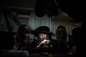 Sukkot preparations: An ultra-Orthodox Jewish man uses a magnifying glass to check an etrog for