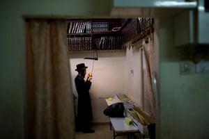 Sukkot preparations: An Ultra Orthodox Jewish man inspects an etrog in Bnei Brak