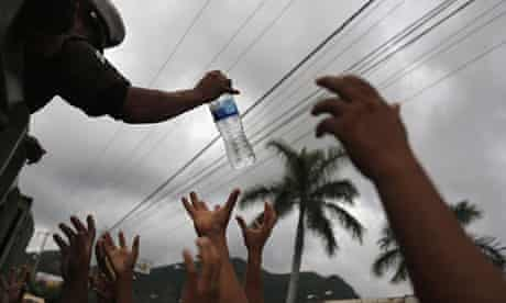 A soldier hands out bottled water to a crowd in Acapulco, Mexico