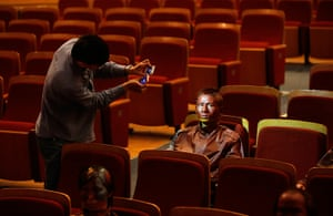 FTA: Jason Lee: A painted participant is lit by two smart phones as an assistant inspects h