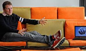 WordPress founder Matt Mullenwegg on an orange sofa pointing at a laptop with WordPress on screen