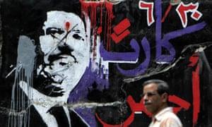 A man walks past graffiti of ousted Egyptian president Mohamed Morsi in central Cairo