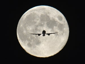 A plane passes in front of a full 'Harvest Moon' as it makes its final approach to landing at Heathrow Airport in west London.
