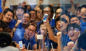 Apple mania: Store staff pose with the new Apple iPhone 5S before its goes on sale at an Apple Store in Tokyo, Japan.