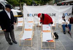 "Supporters of German Chancellor Angela Merkel try out CDU deck chairs that read ""Refreshingly good"" as they arrive for an election campaign event of the German Christian Democratic Union party in Fulda, western Germany on September 19, 2013"