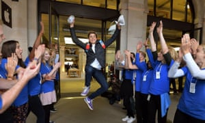 Jesse Green aged 15, from Stanmore jumps for joy as Apple workers applaud him, after being one of the first customers to buy the two new iPhones, at the Apple shop in Covent Garden in London.