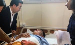 Chinese Ambassador to Kenya Liu Guangyuan (L) delivers condolences to a victim injured in shooting in the Westgate shopping mall on September 21, 2013 in Nairobi, Kenya.