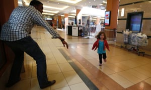 A child runs to safety as armed police hunt gunmen who went on a shooting spree at Westgate shopping centre in Nairobi September 21, 2013.