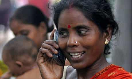 MDG :  Indian slum dweller uses mobile phone in Kolkata