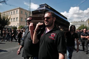 Ex-municipal police officers carry a coffin as they perform a symbolic funeral for the closure of the Municipal Police, during a protest of municipal workers in central Athens, Greece, 23 September 2013.