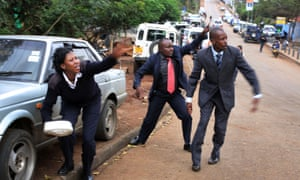 Kenyan security personnel wave at bystanders to take cover as  heavy gunfire erupts from the Westgate Mall in Nairobi Kenya Monday Sept. 23 2013.