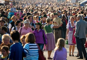 oktoberfest: Visitors walk through a crowded street during sunset