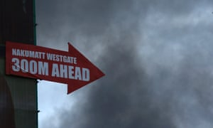 A sign pointing to the direction of Westgate shopping centre is pictured as smoke rises in the vicinity in Nairobi September 23, 2013.