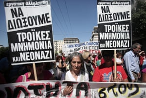 """Protesters carry placards reading in Greek """"Out of austerity measures, Troika, and Neonazi-ists"""" during a protest in central Athens, on Tuesday, Sept. 24, 2013."""