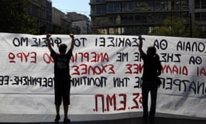 """Protesters raise a banner that reads """" Youths will Beat Fascism"""",  during a protest by striking civil servants in Athens, Tuesday, Sept. 24 2013."""
