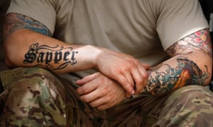 A soldier from the U.S. Army's 1st Platoon, 18th Engineer Company, Task Force Arrowhead rests at Forward Operating Base Mizan in Afghanistan's Zabul Province. The Army is set to introduce a new policy banning tattoos for recruits that show below the elbow and knee and above the neckline