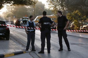 Police officers stand near a tax office following a bomb explosion in Kifisia, a northen suburb of Athens September 26, 2013.