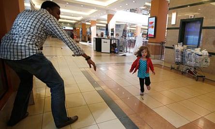 A child runs towards Abdul Yusuf Haji amid a shooting spree at Westgate shopping centre in Nairobi