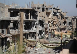 Sheets used as protection from snipers loyal to Syria's President Bashar al-Assad, are hung along a damaged street, in Deir al-Zor September 27, 2013.