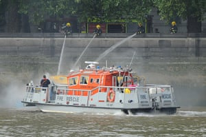 Duck boat on fire: Firefighters work from the north bank of the River Thames, close to Westmin