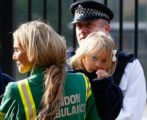 Duck boat on fire: A member of the London Ambulance Service holds a child rescued from the Tha