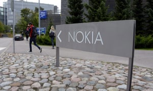 People walk near Nokia sign at the headquarters of Finnish mobile phone manufacturer Nokia in Espoo, Finland on Tuesday morning, Sept. 3, 2013.
