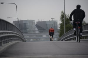 Two cyclists make their way toward the headquarters of Finnish mobile phone manufacturer Nokia in Espoo, Finland Tuesday morning, Sept. 3, 2013.
