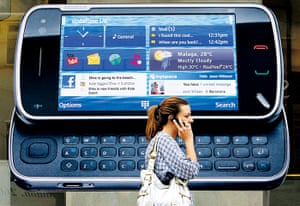 Nokia timeline: 2009: A woman uses her mobile telephone as she passes a Nokia advert for th