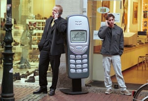 Nokia timeline: c 1998: Men stand near a large model of a Nokia 3210 in Dusseldorf