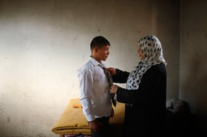 Young newlyweds: The mother of young Palestinian groom Ahmed Soboh, 15, helps him prepare fo