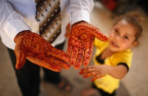 Young newlyweds: Traditional henna designs on the groom's hands. Ahmed works with his father