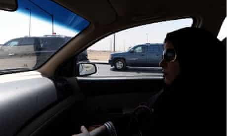 A Saudi Arabian woman sits in a vehicle as a passenger
