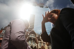 Walkie scorchie: A woman shields her eyes as sunlight is reflected off the building
