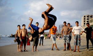 Up and over: young men backflip on the beach in Gaza City.