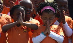 Schoolchildren pray for Nelson Mandela, outside his residence in Johannesburg, South Africa. The former president is continuing to receive medical care at home after leaving the hospital last Sunday.