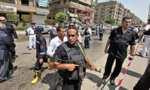 Security officials stand guard at the scene of a bomb blast near the Egyptian interior minister Mohammed Ibrahim's home in Nasr City, Cairo, Egypt. Ibrahim survived the assassination attempt involving bombs set off near his motorcade. It was the first such attack in Egypt in years.