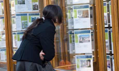 Young woman looking at houses in estate agent window London England UK