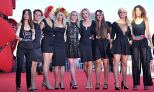 """Femen activists (with their tops on) including Sasha Shevchenko (4th right) and Inna Shevchenko (2nd right) walk on the red carpet with director Kitty Green (5th left) before the screening of """"Sacro Gra"""" presented in competition at the 70th Venice Film Festival."""