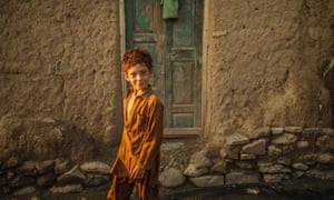 A boy walks past a muddy house in a slum on the outskirts of Islamabad, Pakistan.